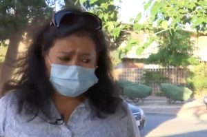 a masked Ana Cardenas speaking about her ordeal to local media