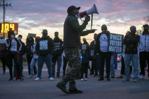 A man with a megaphone addresses demonstrators during a march on Friday in Elizabeth City, N.C.