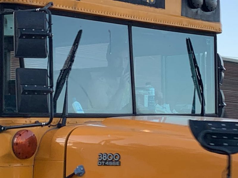 close up of Andrew Loudon in the driver's seat of the school bus wearing a yellow dress