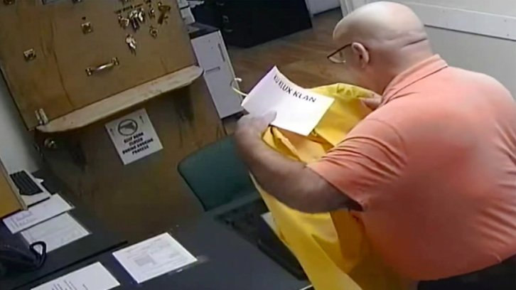 """Police chief Anthony Campo seen placing the """"Ku Klux Klan"""" sign on his Black colleague's yellow raincoat"""