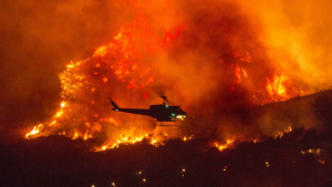 A helicopter prepares to drop water at a wildfire in Yucaipa, CA