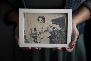 Stacy Cordova holds a framed photo of her aunt Mary Franco, who was sterilized when she was 13 in 1934