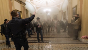 Smoke fills the walkway outside the Senate Chamber as supporters of President Donald Trump are confronted by U.S. Capitol Police officers inside the Capitol in Washington