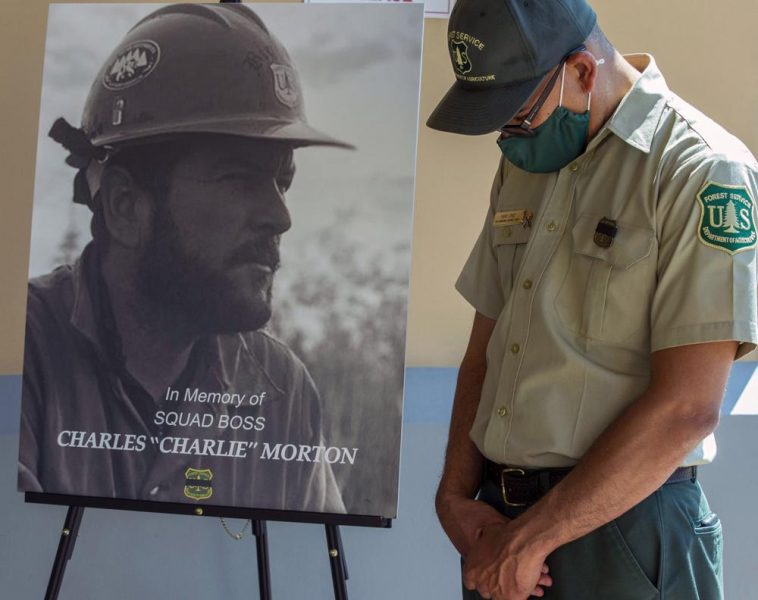 A firefighter lowers his head next to a memorial photograph of Charles Morton, a U.S. Forest Service firefighter killed in the line of duty on the El Dorado Fire.