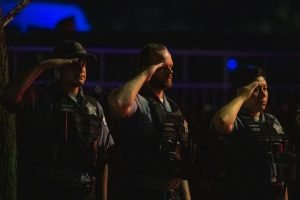 Chicago police officers salute a procession