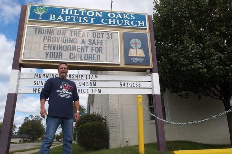 man standing outside sign for Baptist church