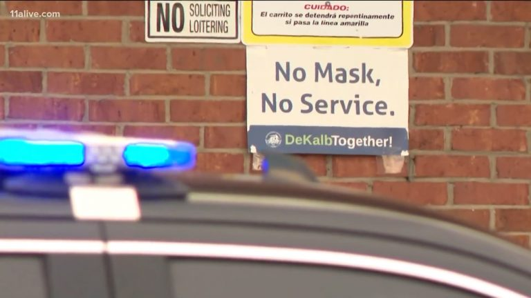 A sign saying 'No Mask, No Service' outside the Big Bear grocery store in DeKalb County above a parked police car