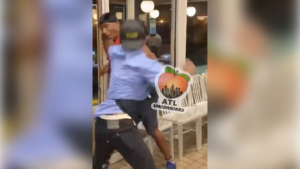 still showing uniformed Waffle House worker throwing punch at another man