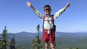 5-year-old hiker Harvey Sutton raising his arms on a mountain top in Bigelow Preserve, Maine, while hiking the Appalachian Trail with his Mom and Dad