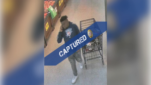 black man in grocery store next to shopping trolley