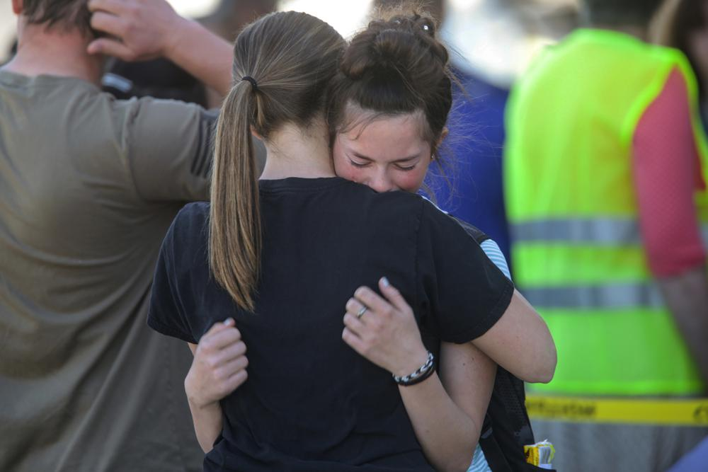 Students comfort each other after a shooting at Rigby Middle School in Rigby, Idaho