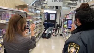 A shoplifter with a bike fills a garbage bag with goods as a woman and a security guard film the incident on their phones