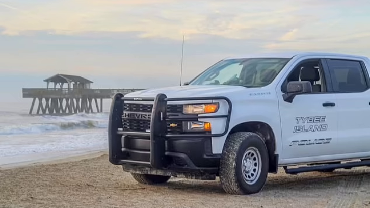 Tybee Island Police vehicle parked on the beach by the water with a pier in the background.