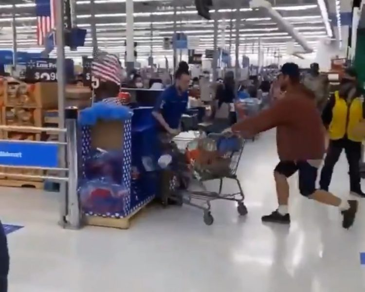 shopper pinning Walmart worker to display case with trolley