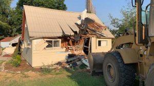 front-end loader by partly destroyed building
