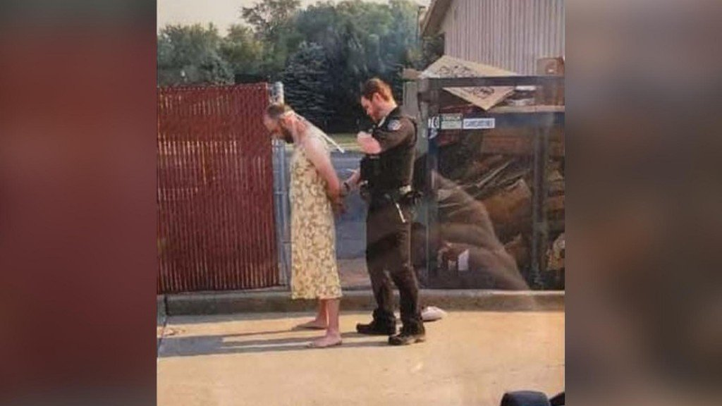 Andrew Loudon wearing a yeloow pattern dress being handcuffed by a police officer