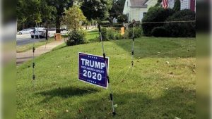 An electric fence surrounds a campaign sign for President Donald Trump in John Oliveira's yard in New Bedford, Mass.
