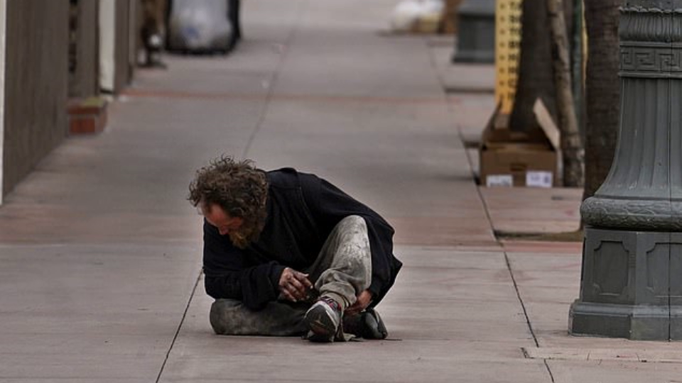 A homeless man sitting on the sidewalk outside Union Station in Los Angeles late last week