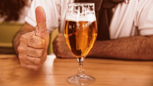 glass of beer with man with doing a thumbs up in the background