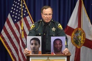 Polk County Sheriff Grady Judd shows mug shots of Chad Berrien, left, and Kevonte' Wilson at a press conference.