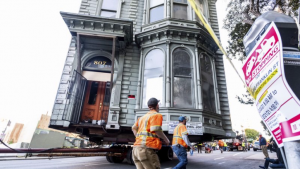 Workers pass a Victorian home as a truck pulls it through San Francisco